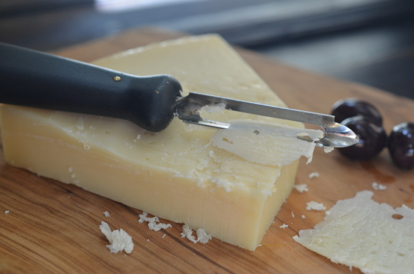 Use a potato peeler to shave off pieces of parmesan cheese.